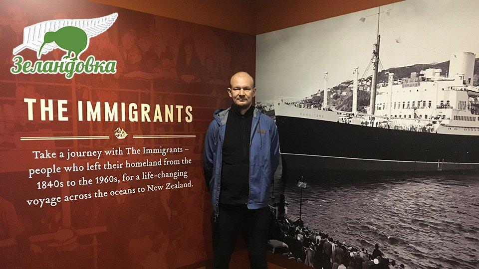 Владимир на фоне постера про новозеландских иммигрантов