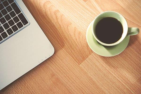 Чашка кофе и ноутбук на столе