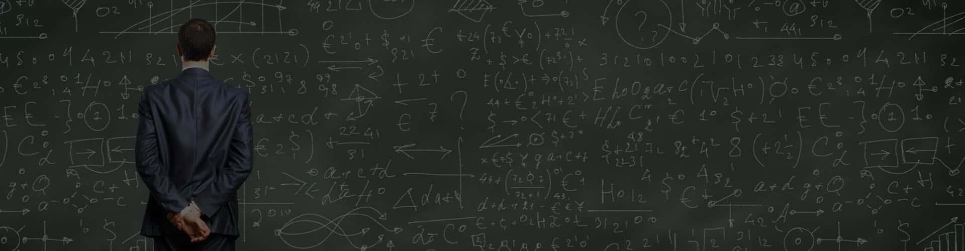 Человек в костюме изучает формулы и графики на доске
